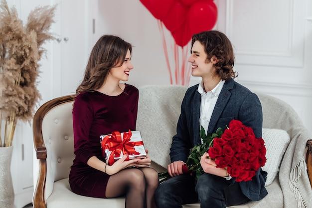 Портрет женщины, держащей подарочную коробку для своего парня, пока он сидит на диване с букетом красных роз