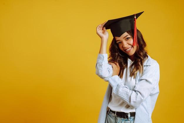Портрет женщины в выпускной шляпе на голове позирует на желтом.