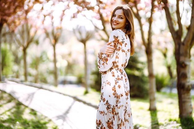 花のきれいなドレスを着た女性の肖像画は、春の日に咲く緑豊かな庭園を楽しんでいます。ファッションとスタイルのコンセプト。