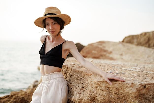 Портрет женщины в черном бюстгальтере и белых брюках, опираясь на скалу на пляже