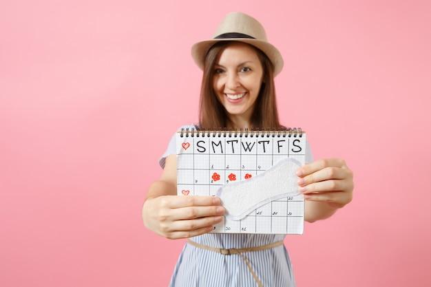 파란 드레스를 입은 여성의 초상화, 생리대를 들고 있는 모자, 분홍색 배경에 격리된 월경일을 확인하기 위한 여성 기간 달력. 의료, 건강 관리, 부인과 개념입니다. 복사 공간