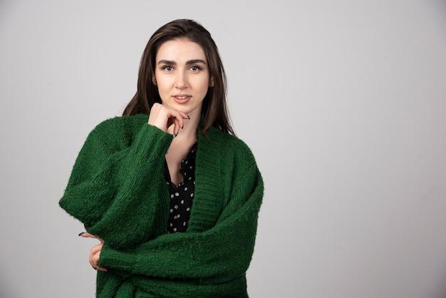 カメラを見ている緑のジャケットの女性の肖像画。