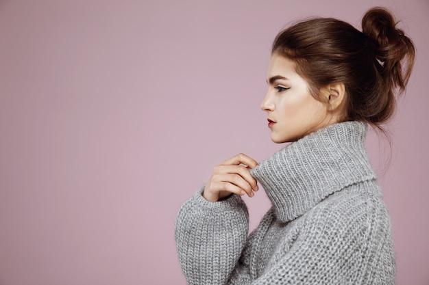 Портрет женщины в сером свитере позирует в профиль на розовом
