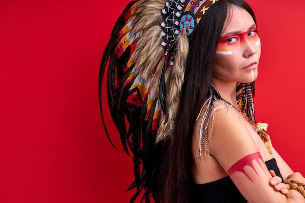 머리에 깃털을 가진 인도 착용 및 화려한 메이크업 포즈에 여자의 초상화