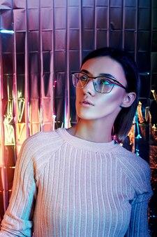 背景にネオン色の反射メガネを着た女性のポートレート。良い視力、女の子の顔に完璧なメイク