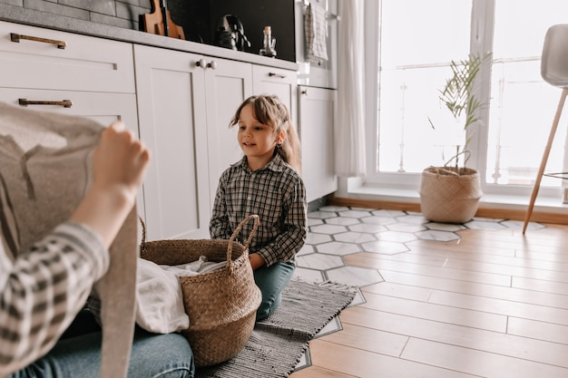 キッチンの床に座って、彼女の母親がバスケットから服を取り出すのを見ている格子縞のシャツを着た女性の肖像画。