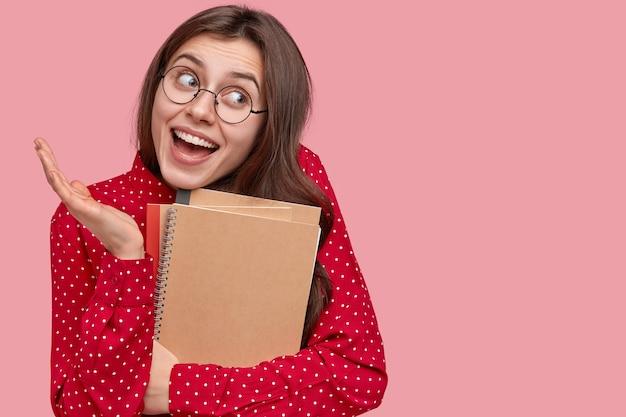 赤いシャツとメモ帳を保持している丸い眼鏡の女性の肖像画