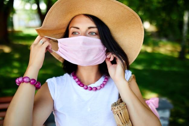 麦わら帽子をかぶった女性の肖像画は、ピンクの保護マスクを脱いで、街の屋外公園で、コンセプトセルフケア、コロナウイルスパンデミック中の生活、検疫を超えて、