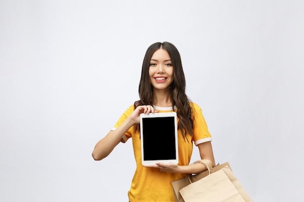 Портрет женщины в летнем платье, держащей пакеты с покупками после покупок в интернете