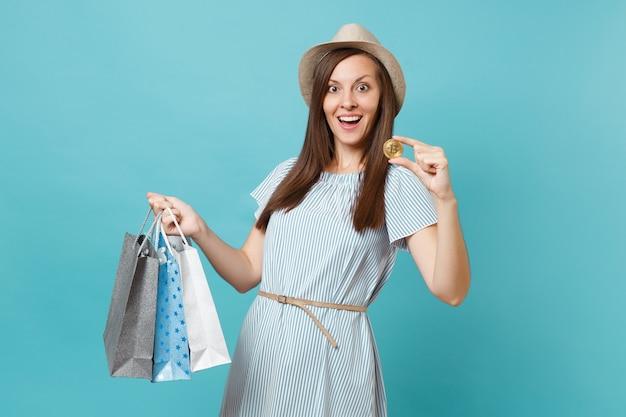 여름 드레스를 입은 여성의 초상화, 쇼핑 후 구매한 패키지 가방을 들고 있는 밀짚 모자, 비트코인, 파란색 파스텔 배경에 격리된 황금색 금속 동전. 광고 공간을 복사합니다.