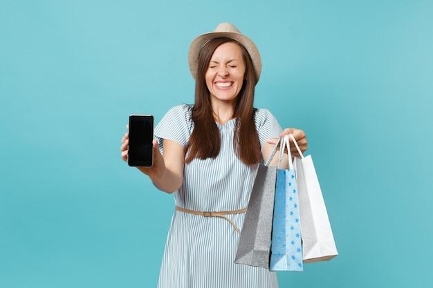 Портрет женщины в летнем платье, соломенная шляпа, держащая пакеты с покупками после покупок, мобильный телефон с пустым экраном, изолированным на синем пастельном фоне. скопируйте место для рекламы.