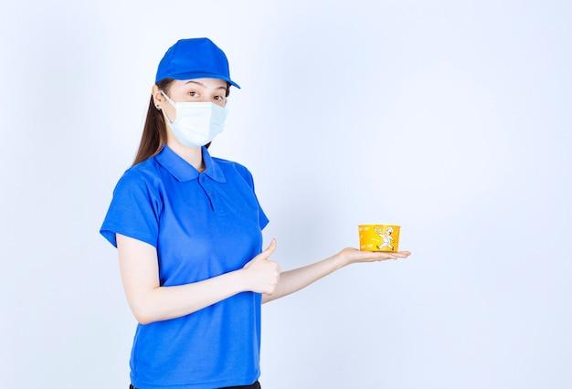 親指を上に示すプラスチック製のコップと制服と医療マスクの女性の肖像画