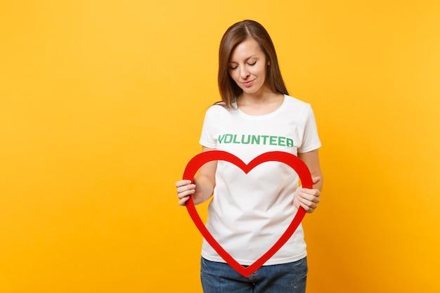 Портрет женщины в белой футболке с письменной надписью зеленым титулом волонтера держит большое красное деревянное сердце, изолированное на желтом фоне. добровольная бесплатная помощь, концепция работы благотворительной благодати.