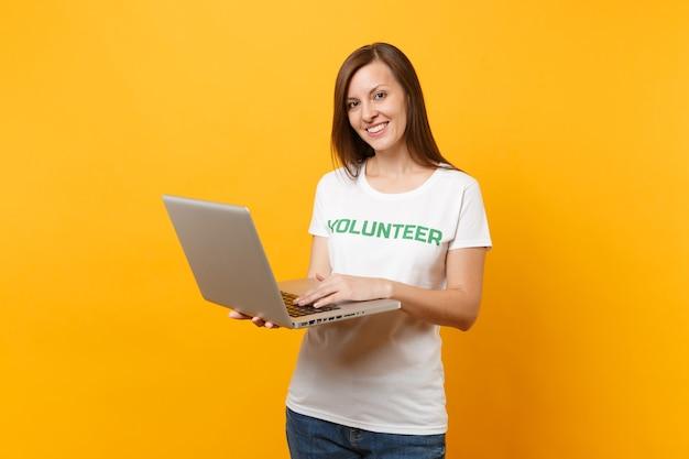 노란색 배경에 격리된 노트북 컴퓨터를 사용하여 녹색 제목이 새겨진 흰색 티셔츠를 입은 여성의 초상화. 자발적인 무료 지원 도움, 자선 은혜 작업 개념.
