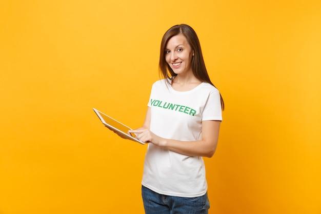 노란색 배경에 격리된 태블릿 pc를 사용하여 녹색 제목 자원 봉사자라고 쓰여진 흰색 티셔츠를 입은 여성의 초상화. 자발적인 무료 지원 도움, 자선 은혜 작업 개념.