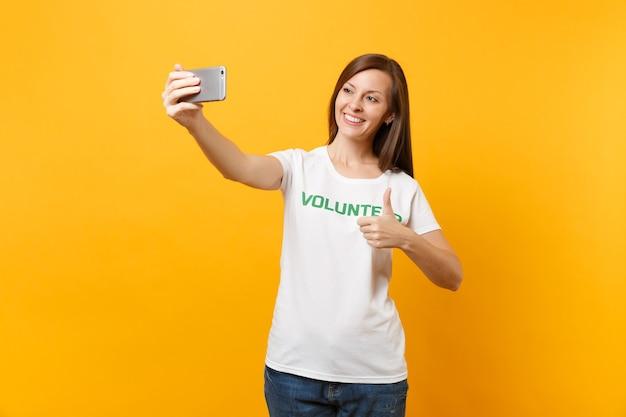 노란색 배경에 격리된 휴대전화로 셀카를 찍는 흰색 티셔츠를 입은 여성의 초상화. 자발적인 무료 지원 도움 자선 은혜 작업 개념