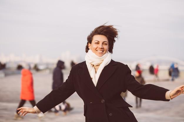 Портрет женщины в зимнем черном пальто и белом шарфе на городской площади.