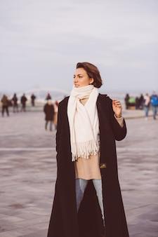 겨울 검은 코트와 도시 광장에 흰색 스카프에 여자의 초상화.