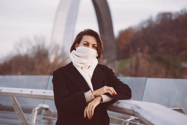 街の広場に冬の黒いコートと白いスカーフの女性の肖像画。