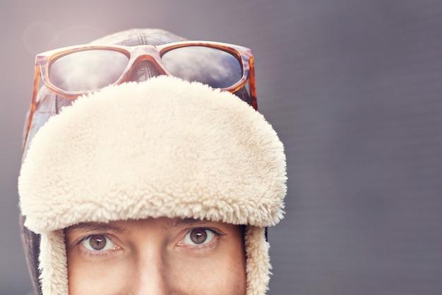 회색 배경 위에 서있는 겨울 모자에있는 여자의 초상화