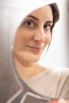 마이크로블레이딩 치료 후 거울을 보고 있는 여성의 초상화