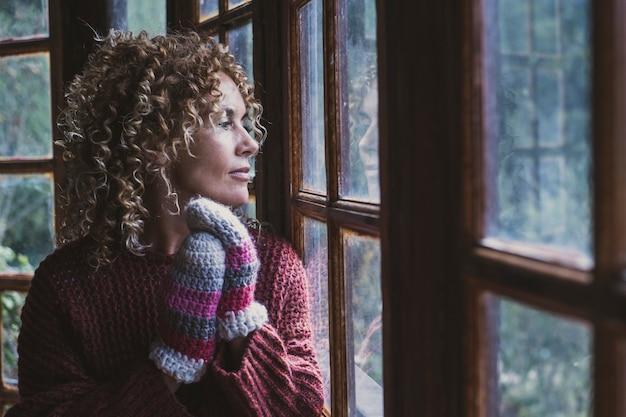 家の外を見ている女性の肖像画