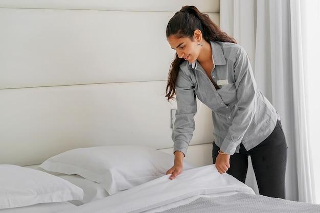 호텔 방에 침대를 만드는 여자 하녀의 초상화. 가정부 만들기 침대
