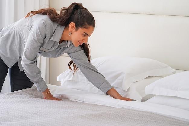 Портрет горничной заправляет кровать в гостиничном номере