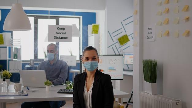 코로나바이러스 감염을 방지하기 위해 얼굴 마스크를 쓴 여성 관리자의 초상화는 비즈니스 사무실 책상 테이블의 의자에 앉아 있습니다. 동료들은 분리된 플라스틱 판을 사용하여 사회적 거리를 유지합니다.