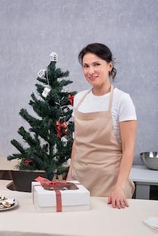새해 나무 옆에 있는 부엌에 선물 상자가 있는 여성 제빵사의 초상화. 수직 프레임.