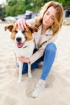 Портрет женщины гладит ее собаку в парке