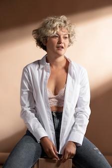白いシャツを着てポーズをとってブラを見せている女性の肖像画