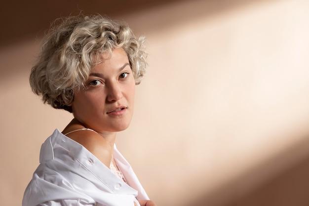 白いシャツでポーズをとる女性の肖像画