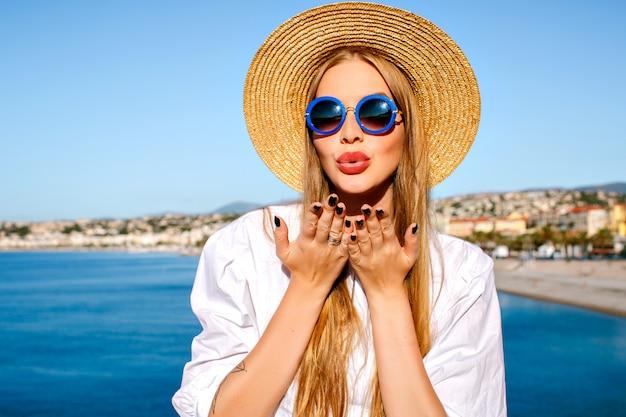 フランスのカンヌシティで青い海に近いポーズの女性の肖像画