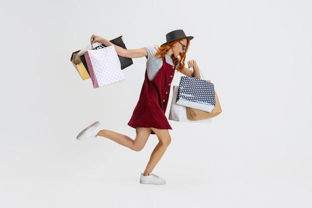 흰색으로 격리된 많은 쇼핑백을 들고 달리는 여성의 초상화