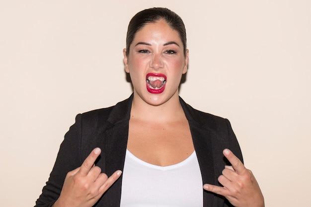 Портрет женщины, показывающей знак рок-н-ролла