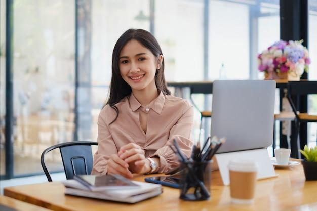 彼女のオフィスに座っている女性の肖像画。魅力的な若い自信のあるビジネスウーマンや会計士は、彼女の大きなプロジェクトのアイデアを持っています。