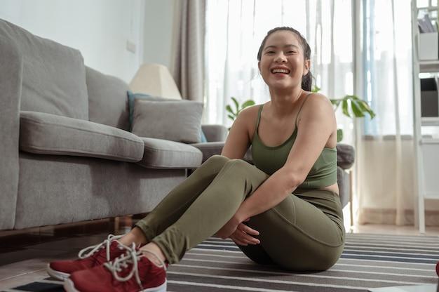 休憩運動のために座っている女性の肖像画検疫運動中に屋内で運動する