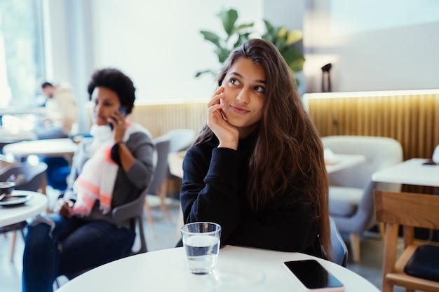 考えて見上げるカフェに座っている女性の肖像画