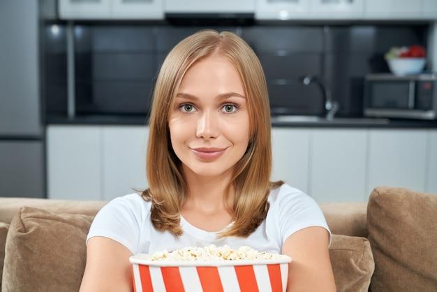 Портрет женщины, сидящей на диване с ведром попкорна