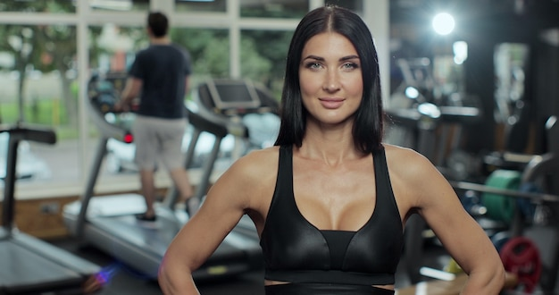 ジムの健康的なライフスタイルのボディービル、フィットネスクラブのアスリートビルダーの筋肉のライフスタイル、幸せなヘルスケアモビリティの概念で運動トレーニングを笑顔の女性の肖像画。