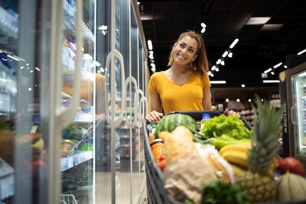 Портрет женщины, стоящей у холодильника супермаркета с тележкой для покупок и улыбающейся