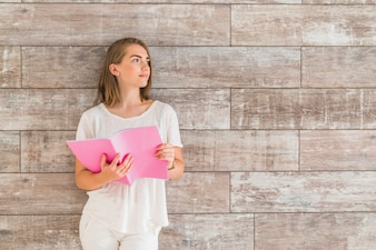 Portrait of woman standing in front of wall holding pink book looking away