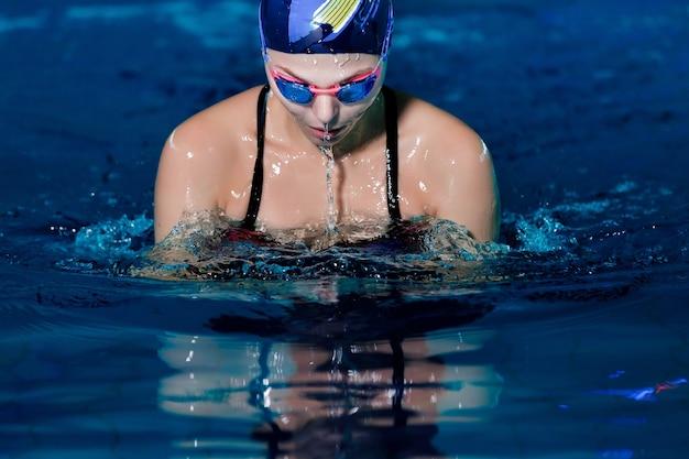 Портрет женщины, плавающей в плавательной шляпе и очках в бассейне