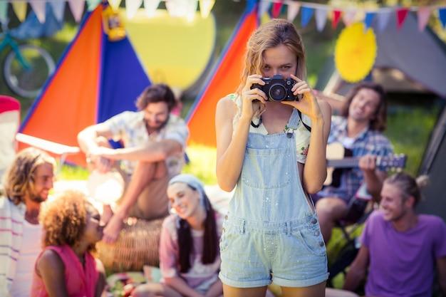キャンプ場で友達の写真を撮る女性の肖像