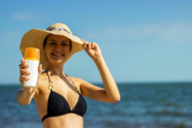 ビーチで日焼け止めローションとスキンケアを取る女性の肖像画