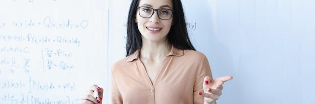 학교 보드 근처에 안경을 쓴 여자 교사의 초상화