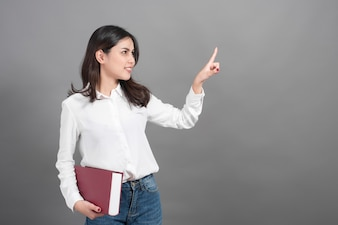 Portrait of woman University student holding book in studio grey background
