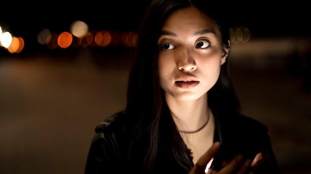 도시의 불빛에 밤에 스마트 폰을 사용하는 여자의 초상화