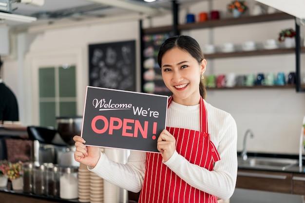 열린 간판을 보여주는 그녀의 커피 숍 게이트에 서있는 여자 웨이트리스의 초상화